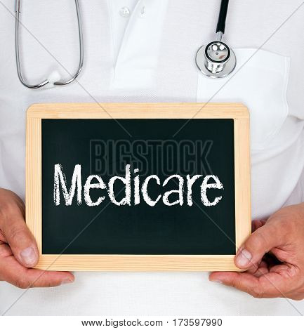 Medicare - Doctor holding chalkboard with text