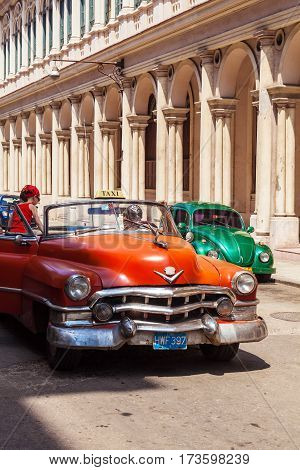 Havana, Cuba - April 1, 2012: Taxi Driver Meets Tourist On Orange Cadillac