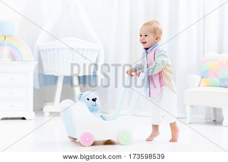 Baby boy learning to walk with wooden push walker in white bedroom with pastel rainbow color toys. Aid toy for child first steps. Toddler kid walking with car wagon. Nursery interior for baby.