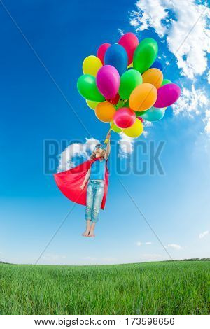 Superhero Child Playing Outdoors In Spring Field