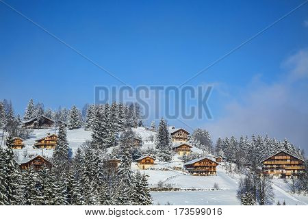 Image of a high altitude wooden chalets covered by snow in Alps.