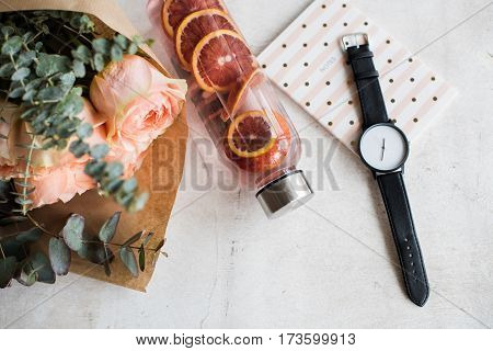 Feminine tabletop, flowers, water with fruits and wrist watch on white textured background
