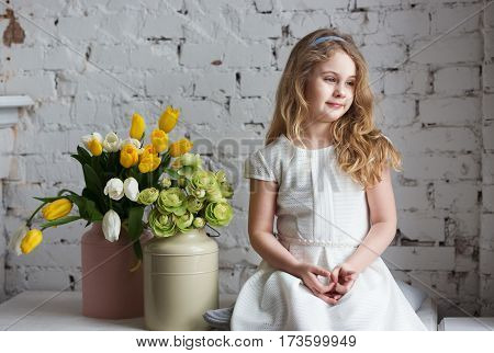 Little blonde girl in a white dress sitting by the window.