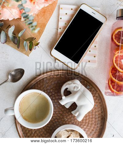 Feminine tabletop, home office with flowers, coffee and smartphone mock-up on white textured background, blogger's workplace