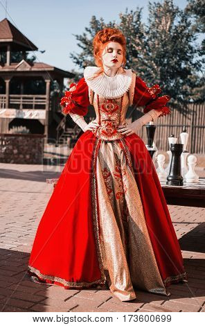 Red Queen in the castle. Red-haired woman in a chic vintage renaissance dress. Fashion Photo of queen. Renaissance woman