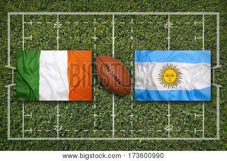 Ireland vs. Argentina flags on green rugby field, 3 D illustration