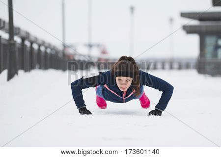 Fitness girl doing pushups during work out fitness at snow winter park, telephoto