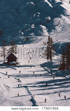 Aerial view of unrecognizable skiers on mountain ski skiing downhill and enjoying winter sport activity