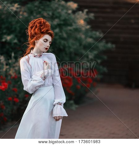 Beautiful baroque red-haired girl with a high hair in an old white dress in the park. The Victorian era. Historic baroque costume. White Queen. Princess castle in baroque style