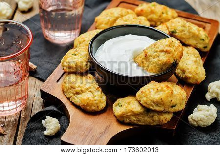 Baked cauliflower Tots on a wood background.