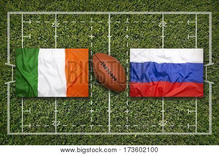 Ireland vs. Russia flags on green rugby field, 3 D illustration