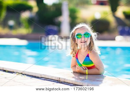 Little girl playing in outdoor swimming pool jumping into water on summer vacation on tropical beach island. Child learning to swim in outdoor pool of luxury resort. Water toy and sunglasses for kids.