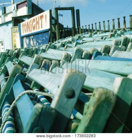Wooden deck chairs for hire stacked on the seafront in Morcambe Lancashire UK.