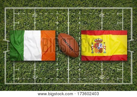 Ireland vs. Spain flags on green rugby field, 3 D illustration