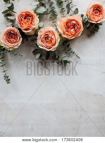 Beautiful beige and orange roses and decorative branches on white textured background, floral arrangement with copy space.