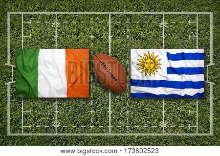 Ireland vs. Uruguay flags on green rugby field, 3 D illustration