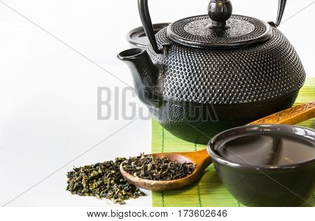 Asian green tea set on bamboo mat with dried green tea in spoon with copy space. Asian tea concept.
