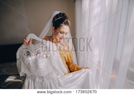 Bride with wedding dress in the room