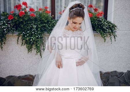 bride in white dress and veil, stands at the walls of the house