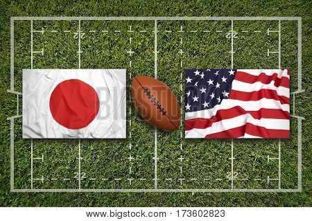 Japan vs. USA flags on green rugby field, 3 D illustration