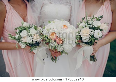 bride and bridesmaid standing with flowers hd