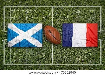Scotland vs. France flags on green rugby field, 3 D illustration