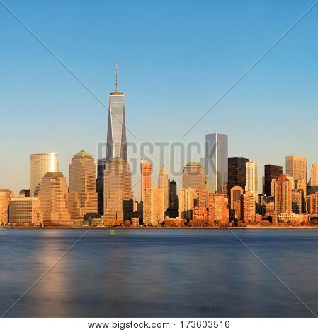 New York City skyline with skyscrapers over Hudson River at sunset viewed from New Jersey