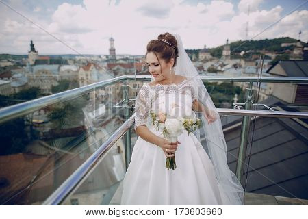 bride standing at the fence and glass in the background is seen the city