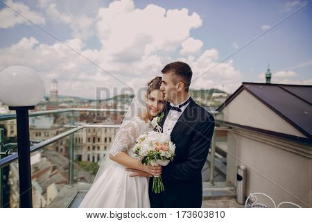 the bride to the groom standing at the fence and glass in the background is seen the city
