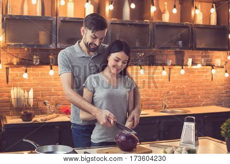 Young beautiful couple in kitchen. Family of two preparing food. Man hugging woman and helping her to cut fresh cabbage. Nice loft interior with light bulbs