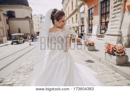 bride in a white dress with a bouquet of peonies and walks across the solar city