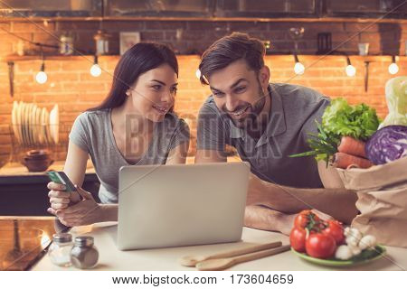Order food online. Young beautiful couple in kitchen ordering food online from restaurant. Family of two using laptop. Young woman paying with credit card. Nice loft kitchen interior with light bulbs