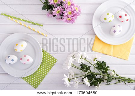 Branches of fresh chrysanthemum with decorative easter eggs on wooden table