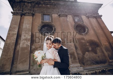 bride and groom standing near the old brown house