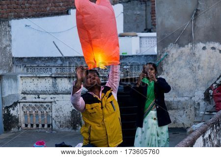 Jaipur, India - 14th Jan 2017 : Family launching a paper lantern from their rooftop during the festival of Makar Sankranti Uttarayan in Rajasthan
