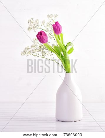 Tulips and gypsophila on white wooden table