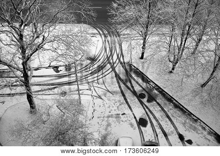 The yard is covered with the first snow, the traces of wheels and legs. View from above