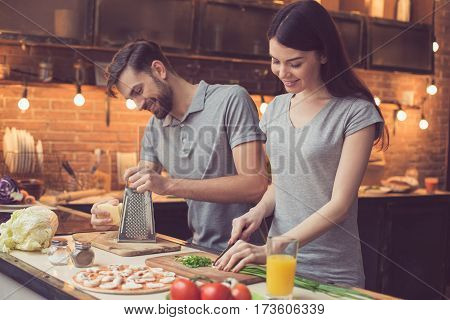 Pizza time. Young beautiful couple in kitchen. Family of two preparing food. Couple making delicious pizza. Man grating cheese. Nice loft interior with light bulbs
