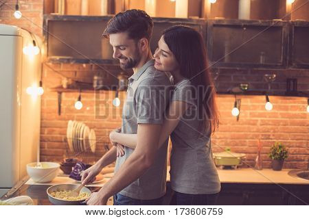 Young beautiful couple in kitchen. Family of two preparing food. Woman hugging man while he making delicious pasta. Nice loft interior with light bulbs