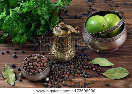 spices parsley lime and pepper mill on a wooden table