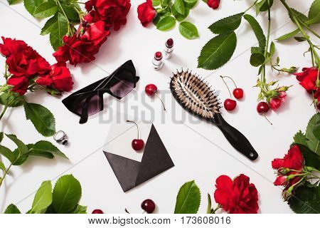 Frame of red beautiful roses with green leaves glamour lady lipstick red tea black glasses a ring with a black stone envelope ripe cherries and a leaf of paper lie on a white background. Flat lay art. Glamour concept