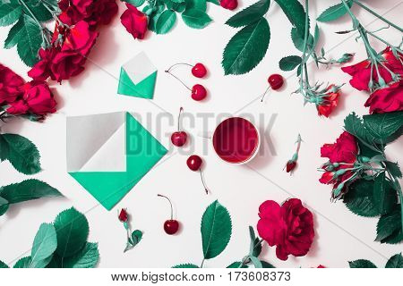 Red roses tea ripe cherries small envelopes with green leaves roses lay on white background. Tea drinking during work. Healing drink. Aromatic morning. Berry compote. Flat lay top view.  Roses flower frame