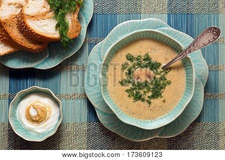 Cheese soup with mushrooms with mustard cream sauce and fresh bread served in original flower-like crockery