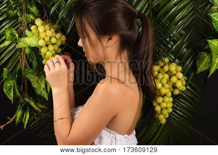 attractive teenager girl holding grapes in studio