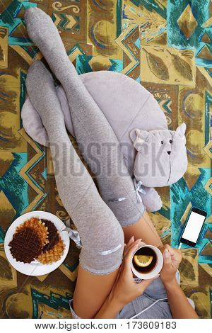 Girl sitting in bedroom in knee-height socks with a cup of tea waffels toy cat and a cell phone