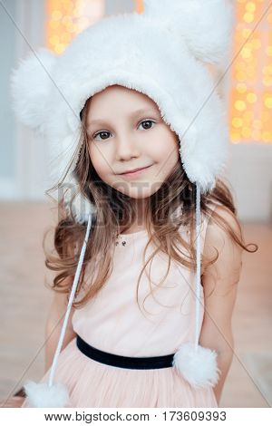 Portrait of adorable smiling child girl wearing fur hat. Fashion photo. Christmas, New Year, birthday, party time. Natural beauty.