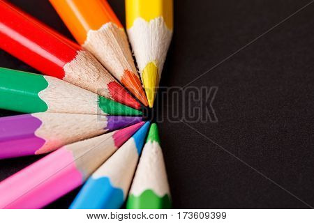 A set of colored pencils on a dark background. Cemicircle of the pencils. Center. Drawing and painting. Artist. Education and school.