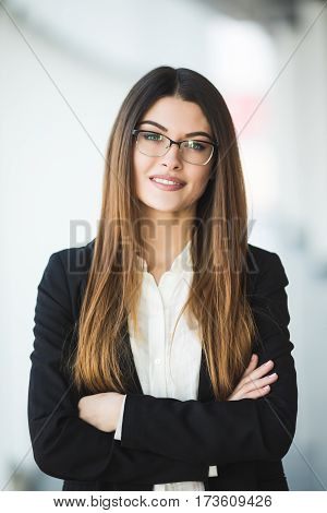 Smiling young Business woman crossed arms, standing against office with panoramic windows