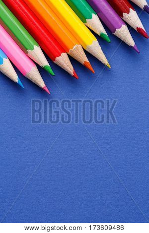 Colored pencils angle. Many different colored pencils on blue background. School and education. Drawing and painting. Art and design.