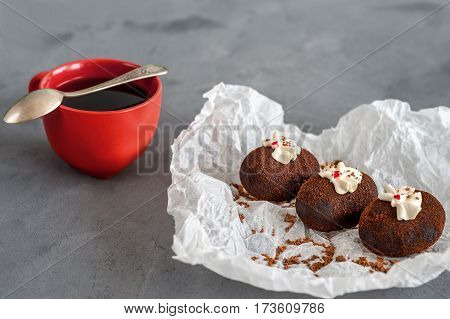 Cakes made of chocolate on a white transparent paper on a gray background. Cakes decorated with red jelly and delicate white cream. Red cup of coffee. A metal spoon.